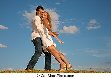 man holds the woman on the meadow