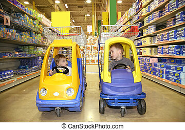 children in the toy automobiles in the store