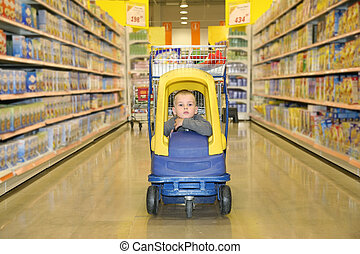 boy in the toy automobile in the supermarket