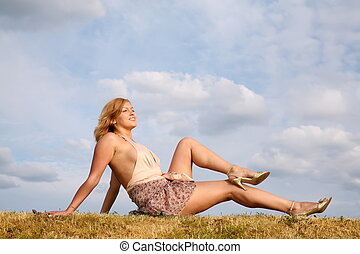 young woman in the dress sits on to the meadow