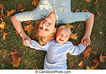 blue-eyed blond lies with the son on the earth at the park in autumn