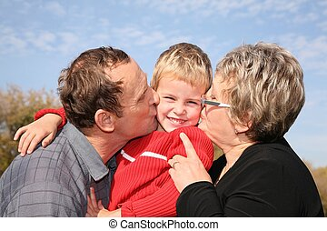 grandmother and grandfather kiss the grandson