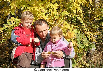 grandfather with the grandson and granddaughter in park in autumn