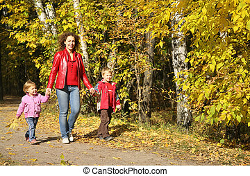 mother with the children goes for a walk in the park in autumn