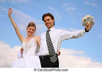 happy wedding couple on sky