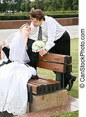 bride sits on the bench and looks at the fiance