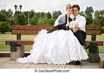 bride with the fiance they sit on the bench