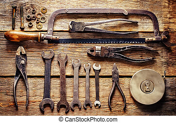 old tools, wrenches on a dark wood background tinting...