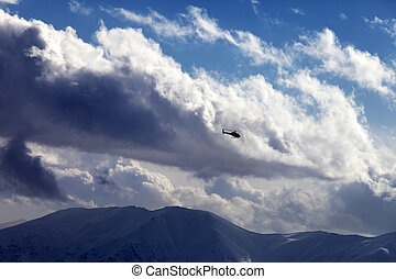 Helicopter in cloudy sky and winter mountains. Ski resort...