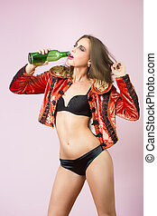 sexy woman drinks alcohol. green bottle - sexy woman in...