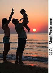 Mummy with daughter and grandfather on sunset at sea