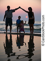 Mother with children and grandfather ashore on sunset