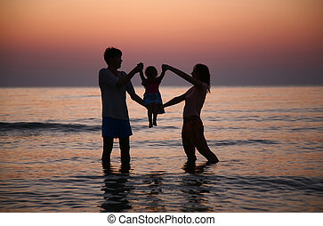 Father with mother hold child in sea on sunset