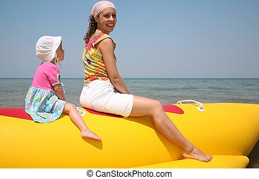 mother with the daughter they sit on the inflatable boat