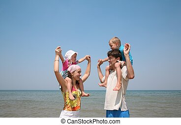 parents hold children on the shore of the sea