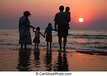 Grandfather with grandmother and the children against the background of sunset in waves