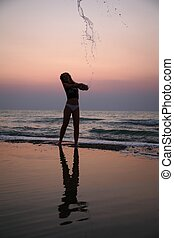 Young woman sprinkles by water on beach on sunset