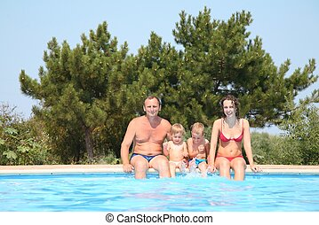 Woman and man with children at the pool board