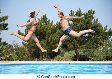 Woman and man jump over pool