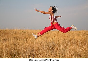 young woman jump on the meadow