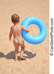 The girl with a lifebuoy ring goes on sand