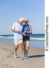 Healthy Senior Couple Running Jogging on Beach - Happy...