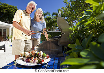 Happy Senior Couple Outside Cooking on A Summer Barbecue -...