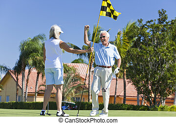 Happy Senior Couple Playing Golf and Putting Together -...