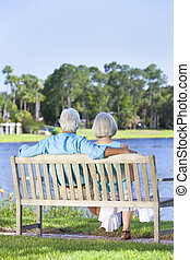Rear View Senior Couple Sitting On Park Bench - Rear view of...