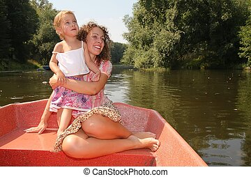 mother embraces daughter in the boat
