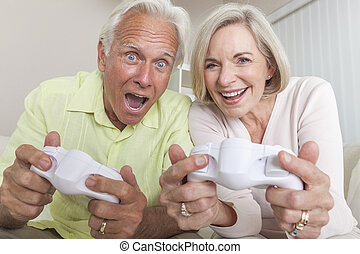 Senior Man and Woman Couple Playing Video Console Game -...