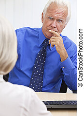 Thoughtful Senior Businessman In Office at Desk - Thoughtful...