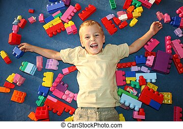 boy laying on floor in playroom