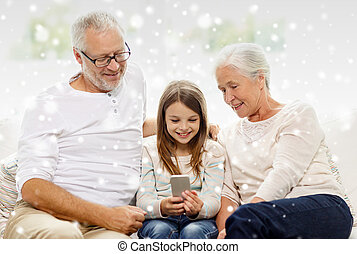 smiling family with smartphone at home - family, generation,...
