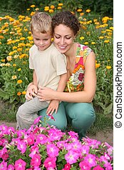 mother and son look on flowers
