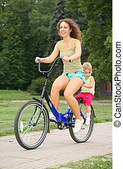 Mother and daughter ride on bicycle