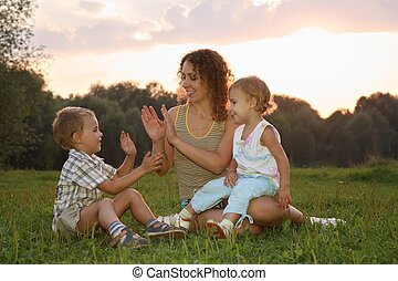 mother with children sits on the grass and play