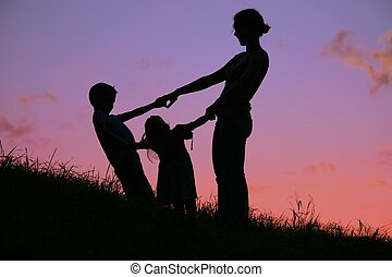 mother and children are held for the hands on the sunset