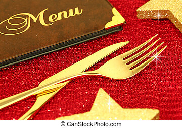 Christmas golden cutlery and restaurant menu on festive...