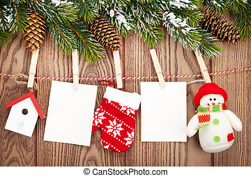 Snow fir tree, photo frames and christmas decor on rope over...