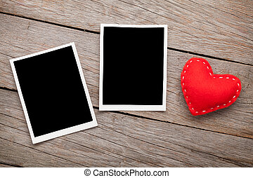 Two photo frames and valentines day toy heart over wooden...