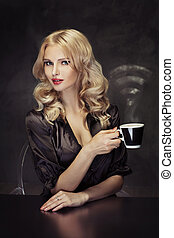Beautiful woman holding the vaporous cup of coffee -...