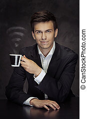 Smart young businessman holding the cup of vaporous coffee -...