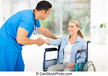 mid age medical doctor greeting disabled patient - friendly...