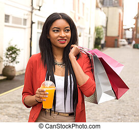 young woman enjoying a smoothie with shopping bags.