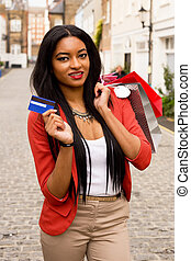 young woman showing a credit card holding shopping bags