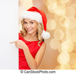 smiling young woman in santa hat with white board - winter...