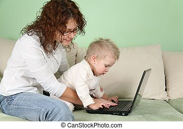 young woman in eyeglasses with notebook and child on sofa