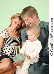 child with book and parents