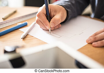 Architect working at his desk drawing a sketch.